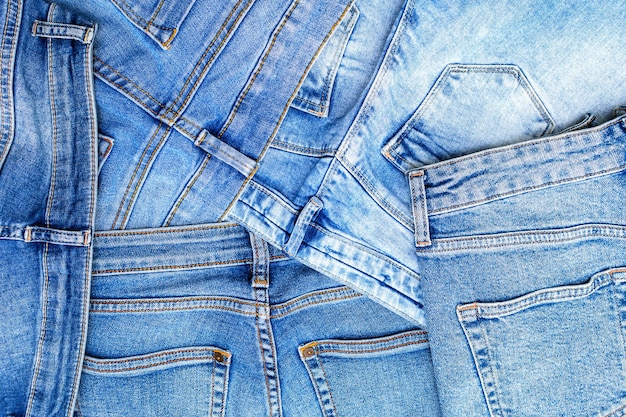 Denim texture background, pile of jeans, light blue surface of cotton fabric with pockets and seam with orange thread stitches