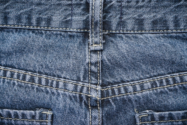 Denim texture fabric with a seam of fashionable design, space for text. selective focus. classic jeans background.