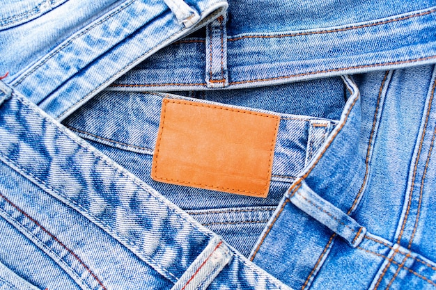 Denim texture, pile of blue jeans and blank leather label close up, variety of comfortable casual pants and clothes
