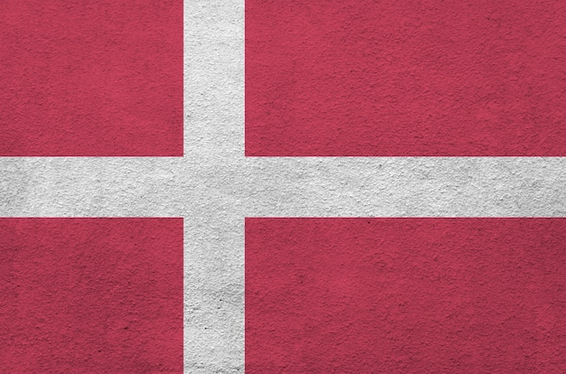 Denmark flag depicted in bright paint colors on old relief plastering wall. textured banner on rough background