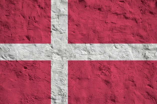 Denmark flag depicted in bright paint colors on old relief plastering wall.