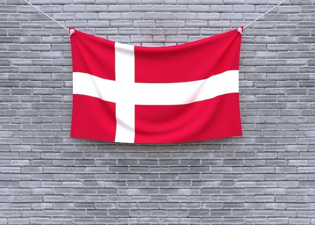 Denmark flag hanging on brick wall