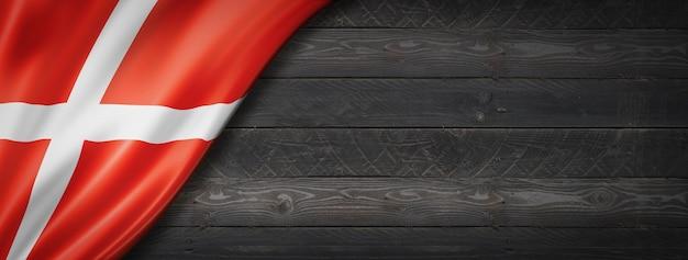黒い木の壁にデンマークの旗。水平方向のパノラマバナー。