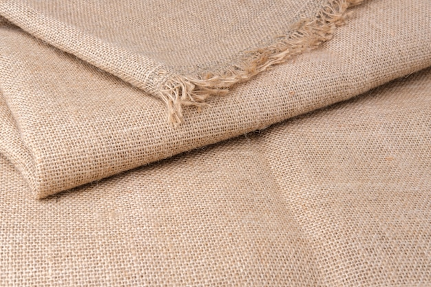 A dense burlap fabric is spread on the table. the packaging material is folded in several layers with fringes along the edges. cloth for sewing and diy products.