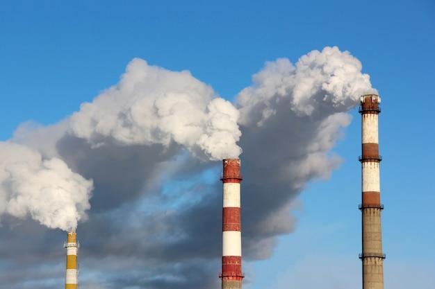 Густые облака дыма или пара из трех заводских труб на фоне голубого неба. понятие экологии, загрязнения окружающей среды.