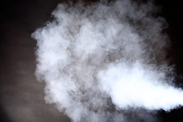 黒い背景に白い煙と霧の濃いふわふわのパフ、抽象的な煙の雲、動きがぼけて焦点が合っていない、壁の丸い形に