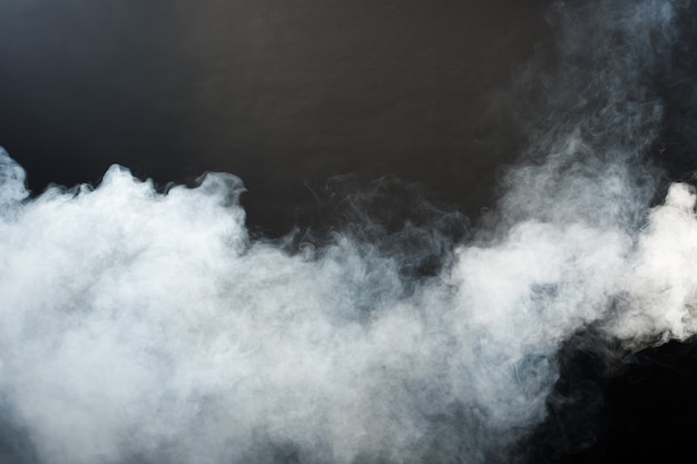 검은 배경에 흰 연기와 안개의 짙은 솜털 퍼프, 추상 연기 구름, 초점이 흐릿한 움직임. 기계 드라이아이스의 연기가 날리고 공기 중에 펄럭이는 효과 질감