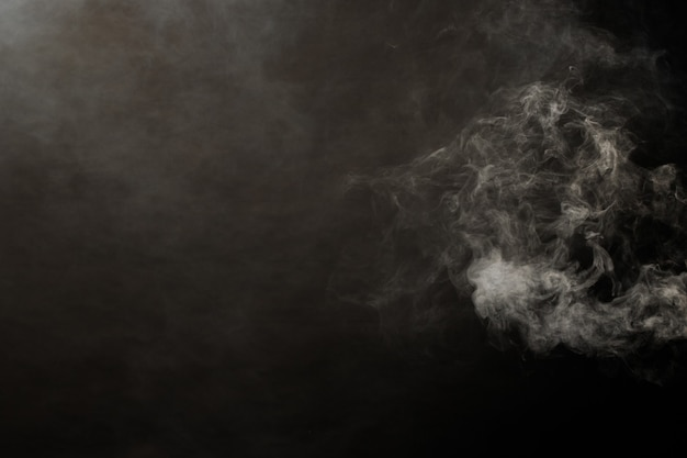 Dense fluffy puffs of white smoke and fog on black background, abstract smoke clouds, movement blurred out of focus. smoking blows from machine dry ice fly and fluttering in air, effect texture