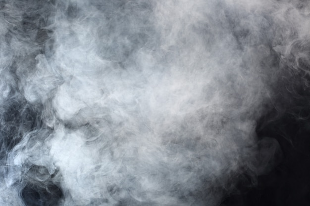 Dense fluffy puffs of white smoke and fog on black background