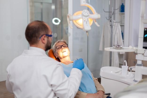 歯科医院で高齢患者の歯を修復するキャビネット内のデンスティス。オレンジ色の機器を備えた歯科医院の歯科医による診察中の高齢患者。