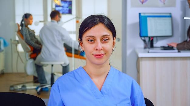 Ассистент стоматолога, глядя на камеру, пока врач осматривает пациента в фоновом режиме. профессиональная медсестра стоматолога улыбается на веб-камеру, сидя на стуле в зале ожидания стоматологической клиники.
