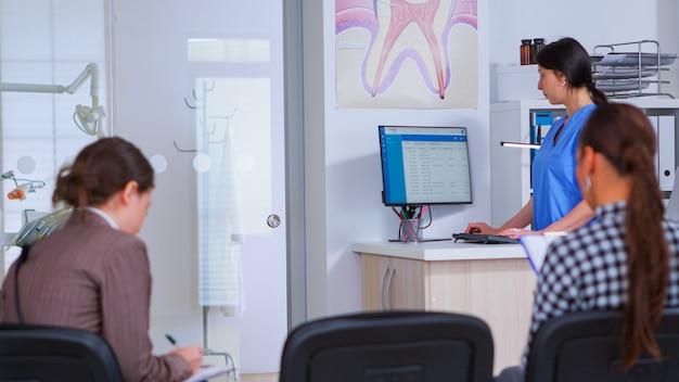 女性が登録フォームに記入するのに助けを求めている間に予約をする歯科助手。混雑した専門歯科矯正医院の待合室の椅子に座っている患者。