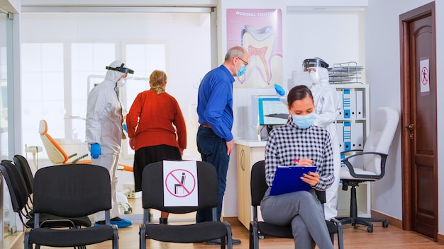 患者の体温を測定した後に記入するフォームを提供するコロナウイルスに対するつなぎ服を備えた歯科助手。口内科クリニックの登録書類に顔面保護マスクを書いている患者
