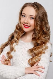 歯科、美容、髪型、人々のコンセプト-長いカールした髪の美しいモデルのブルネット。女の子の大きなネックレスビーズとチェーン。宝石。髪型の波状のカール。中かっこ、歯科の女の子