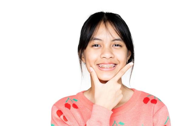 笑顔と白い背景の上のカメラを見ている歯列矯正器の女の子、彼女は幸せを感じ、歯科医との良い態度を持っています。彼らが歯科医院に行かなければならないとき、恐れない子供たちを動機づけてください。