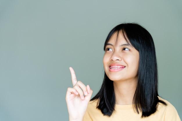 笑顔でカメラを見ている歯列矯正器の女の子、彼女は幸せを感じ、歯科医との良い態度を持っています。彼らが歯科医院に行かなければならないとき、恐れない子供たちをやる気にさせてください。