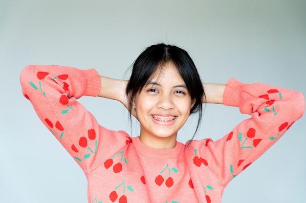 笑顔でカメラを見ている歯列矯正器の女の子、彼女は幸せを感じ、歯科医との良い態度を持っています。彼らが歯科医院に行かなければならないとき、恐れない子供たちを動機づけてください。