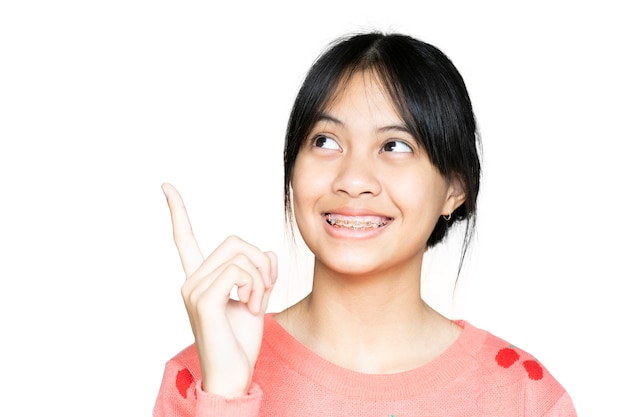 Dental brace girl smiling and looking to camera on white background, she feel happy and have good attitude with dentist.  motivate kids not fear when they have to go to dental clinic.