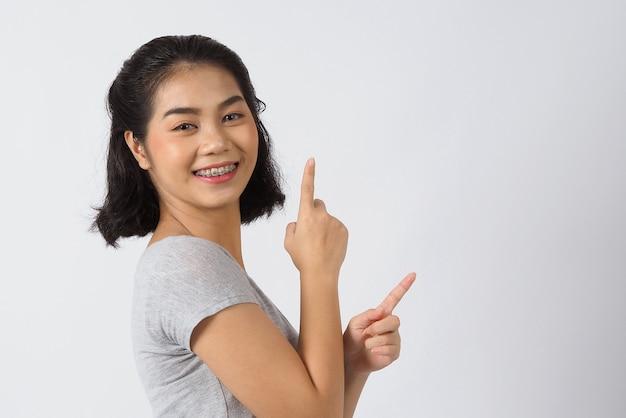 Стоматологическая скоба предназначенная для подростков девушка улыбается, глядя на камеру. белые зубы с синими скобами. стоматологическая уход. улыбка азиатской женщины с ортодонтическими принадлежностями. эстетическая стоматология, ортодонтическое лечение. студийный снимок.