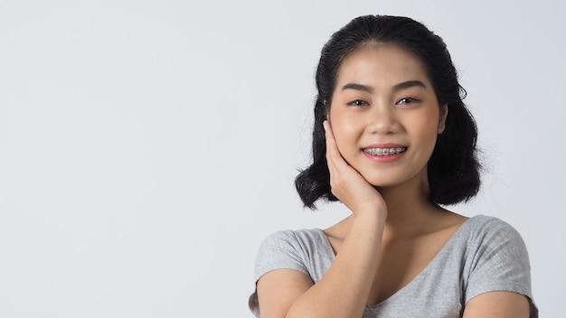 Стоматологическая скоба предназначенная для подростков девушка улыбается, глядя на фронт. белые зубы с синими скобами. стоматологическая уход. улыбка азиатской женщины с ортодонтическими принадлежностями. брекеты для полости рта.