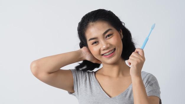 Улыбка девушки-подростка стоматологической скобки, держащая зубную щетку. белые зубы с синими скобами. стоматологическая помощь. азиатская женщина с контактными линзами и ортодонтическими принадлежностями. косметическая стоматология.