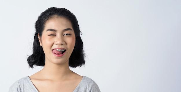 중괄호 치아와 콘택트 렌즈를 착용하는 십대 아시아 여성의 치과 교정기 그녀는 매우 자신감이 넘치고 자랑스럽게 자신을 제시하고 흰 벽에 미소를 지으며 웃고 있습니다.