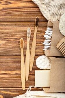 Стоматологическая помощь бамбуковые зубные щетки мыло, туалетные принадлежности на деревянном столе. деревянное банное изделие.