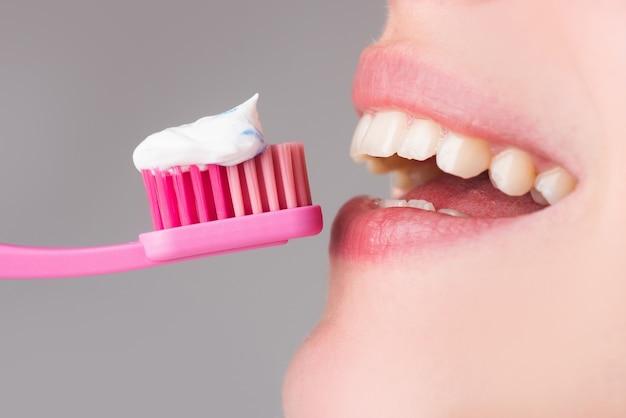Стоматологическая помощь крупным планом. женщина, чистящая зубы. крупный план на счастливой молодой женщине, чистящей зубы щеткой.