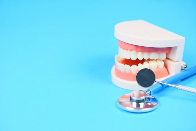 Концепция стоматологической помощи - инструменты стоматолога с зубными протезами, инструменты для стоматологии и гигиена зубов и проверка оборудования с моделью зубов и ротовой полостью рта