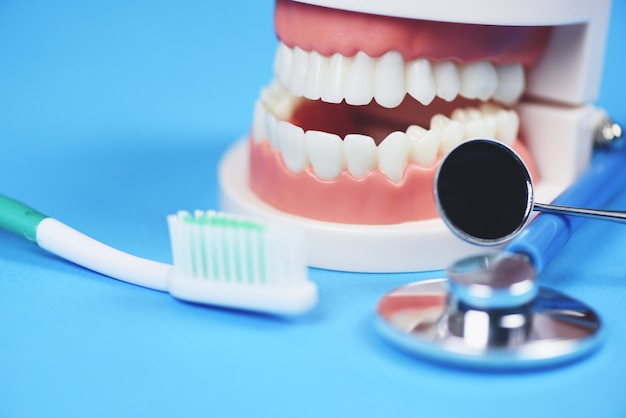 Dental care concept - dentist tools with dentures dentistry instruments and dental hygiene and equipment checkup with teeth model and mouth mirror oral health
