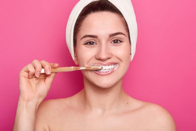 치과 치료 개념. 기쁘게 젊은 여자는 하얀 미소 치아 빛나는 미소, 나무 칫솔과 치아 미백 치약, 분홍색 벽 위에 절연 치아를 청소, 자연의 아름다움이 있습니다.