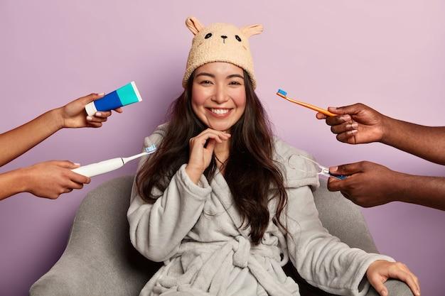 Cure odontoiatriche e concetto di igiene orale con giovane donna dai capelli scura positiva