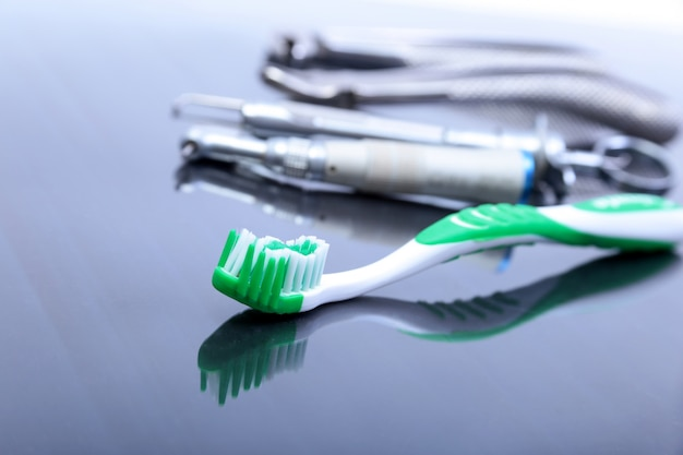 Dental care toothbrush with dentist tools on mirror background.