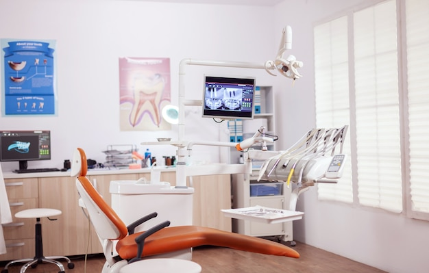 Poltrona odontoiatrica e altri accessori utilizzati dal dentista in armadietto vuoto. armadio per stomatologia senza nessuno dentro e attrezzatura arancione per il trattamento orale.