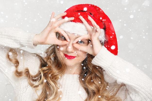 치과, 크리스마스, 크리스마스, 겨울, 행복 개념 - 산타 도우미 모자를 쓴 웃는 여자, 아름다운 여성 모델은 산타 모자를 착용합니다. 교정기를 든 소녀, 치과