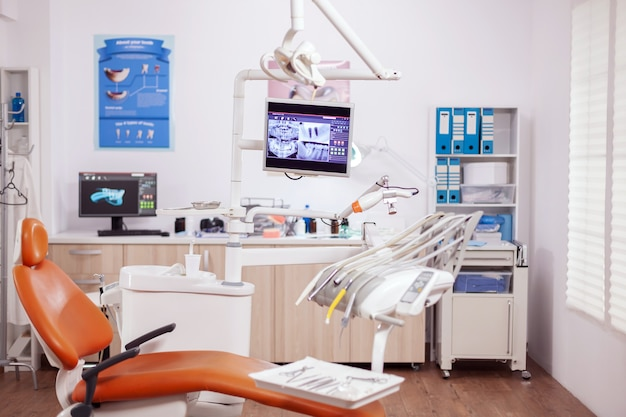 オレンジ色のモダンな歯科用機器を備えた歯科医院のインテリア。誰も入っていない口腔病学用キャビネットと、口腔治療用のオレンジ色の器具。