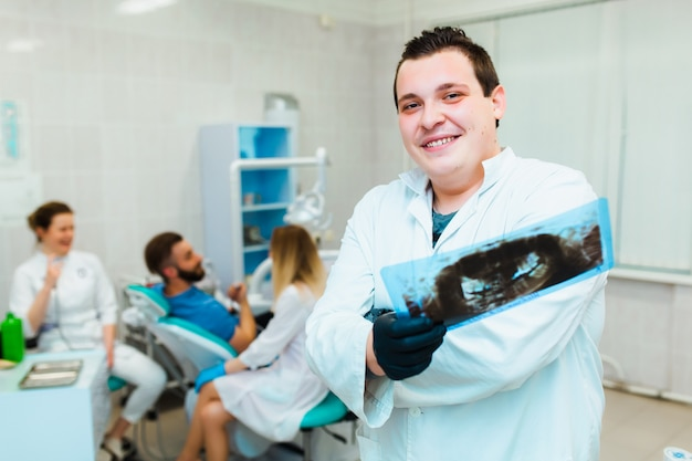 Dental clinic. portrait of a professional dentist on the background of a working team of doctors. concept of medical education and medical insurance.