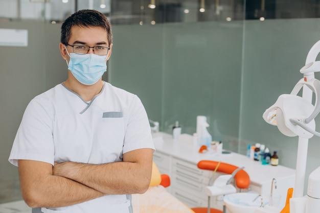 마스크를 쓰고 병원에 서있는 치과 의사