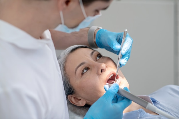 Dental drill. dentist working on patients teeth restoration and making dental drilling