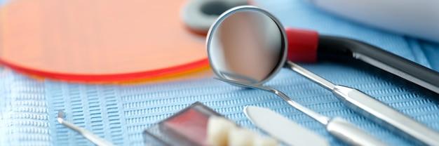 歯科機器は、歯科医院のクローズアップの背景のテーブルの上の青いナプキンにあります