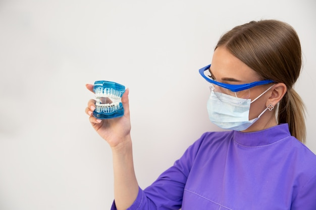 치과 검사, 치열 교정 의사가 클리닉에서 치아와 교정기를 확인합니다.