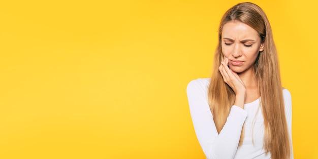 歯科女性の健康。重度の歯痛を持つ悲しいブロンドの髪の若い女性の肖像画