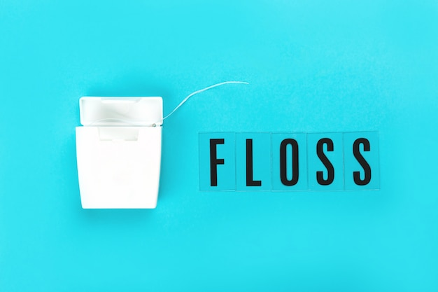 Dental floss on blue pink background.
