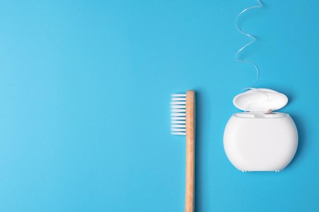 파란색 배경에 치실 컨테이너 및 대나무 칫솔. 매일 구강 위생, 치아 관리 및 건강. 구강 청소 제품. 치과 치료 개념. 텍스트 또는 로고를위한 빈 곳