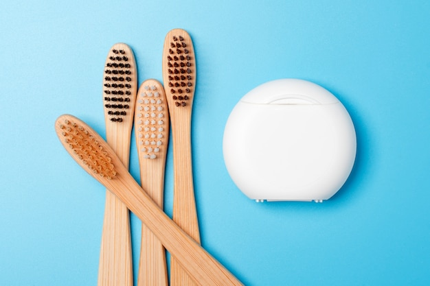 파란색 배경에 치실 컨테이너 및 대나무 칫솔. 매일 구강 위생, 치아 관리 및 건강. 구강 청소 제품. 치과 치료 개념.