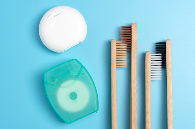 Dental floss containers and bamboo toothbrushes on blue background. daily oral hygiene, teeth care and health. cleaning products for mouth. dental care concept.
