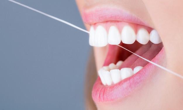 デンタルフロス-女性のデンタルフロスの歯。デンタルフロス。歯の世話をします。健康な歯のコンセプト。デンタルフロス。口腔衛生とヘルスケア。笑顔の女性はデンタルフロスの白い健康な歯を使用しています。