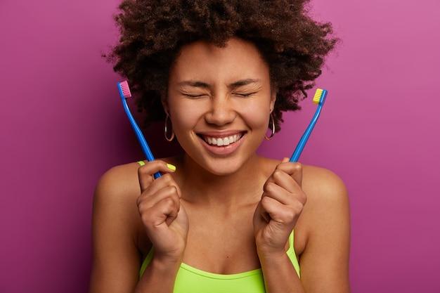 歯科の健康と衛生の概念。黒い肌の巻き毛の女性は目を閉じ、白い健康な歯を見せ、2つの歯ブラシを持ち、朝の日課を楽しんで、紫色の壁に向かって屋内に立っています。