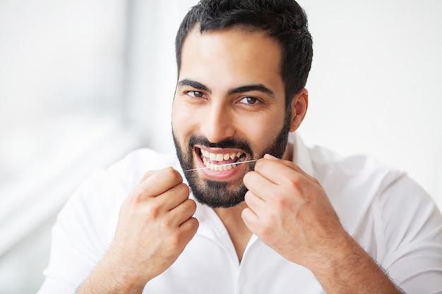 Здоровье зубов. человек с красивой улыбкой чистя здоровые зубы зубной нитью. изображение высокого разрешения.