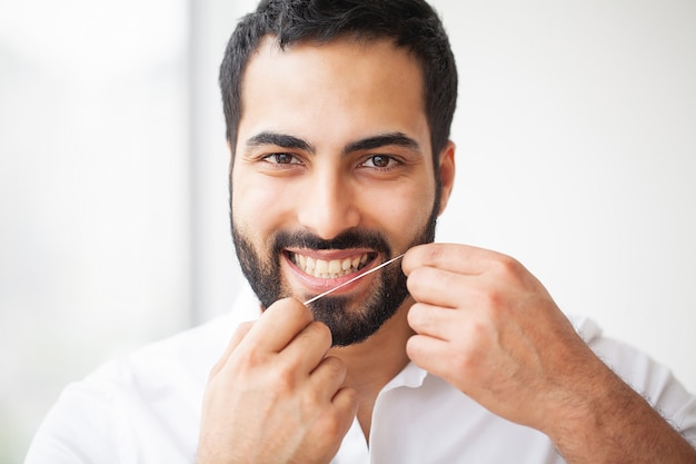 Dental health. man with beautiful smile flossing healthy teeth